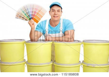 Cheerful male decorator holding a color swatch and standing behind a stack of color buckets isolated on white background