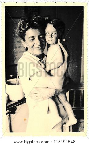 Vintage photo of mother and baby. Photo with dark tint circa 1941.