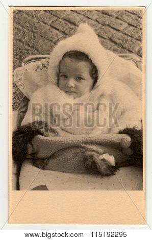 Vintage photo shows a baby girl in a pram (baby carriage) circa 1940.