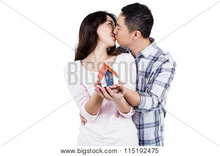 Couple kising while holding a model house against white background