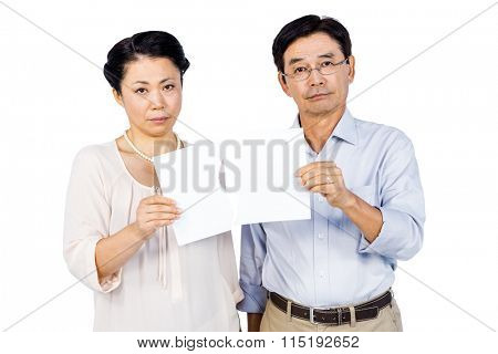 Couple holding torn paper on white background