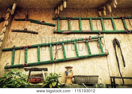 The Wall Of Shed With Ladders, Various Tools And Dried Corn