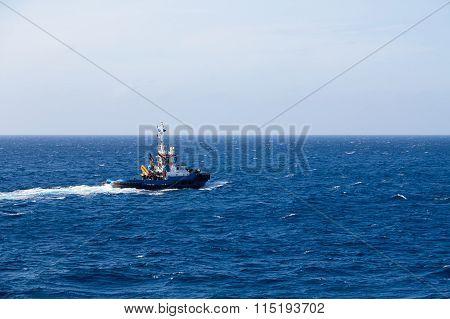 Blue Tugboat Heading Out Over Blue Sea
