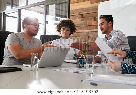 Young Office Workers Discussing Work In A Boardroom