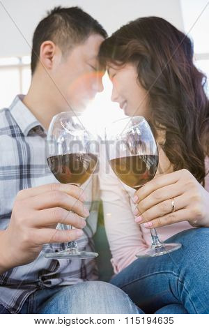 Low angle view of couple holding wineglasses while sitting at home