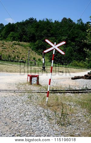 Railroad Crossing Sign In The Nature With Rusty Wagons And Sleepers In The Background