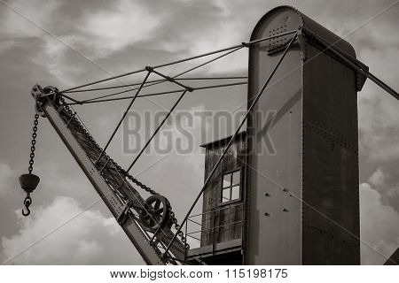 Old ancient wooden elevator crane in harbor.