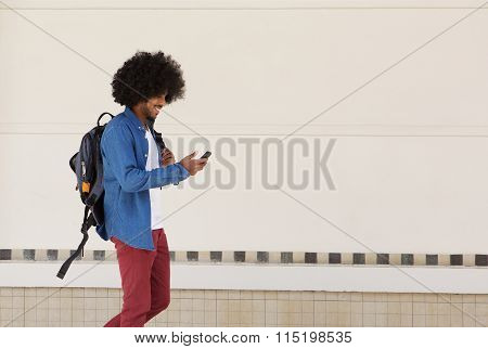 Male Student Walking With Bag And Mobile Phone