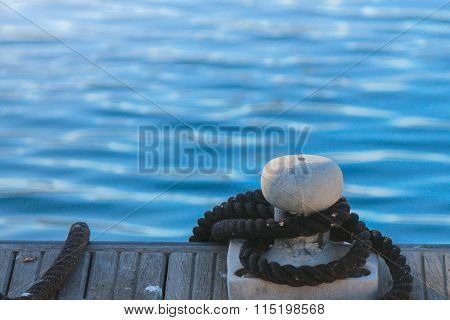 Docks With Ropes In Harbor, Blue Background With Copy Space.