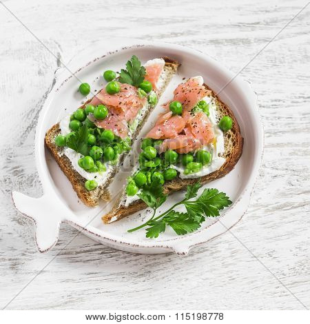 Open Sandwich With Soft Cheese, Green Peas And Smoked Salmon. A Delicious Breakfast Or Snack
