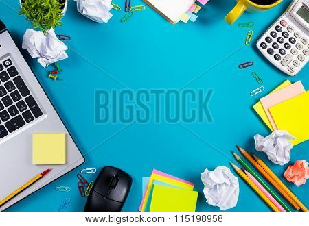 Office table desk with set of colorful supplies, white blank note pad, cup, pen, pc, crumpled paper,