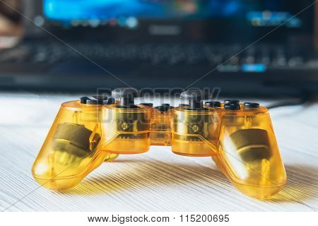 Yellow Transparent Joystick And A Laptop With A Video Game On A Table