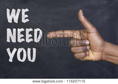 Male hand pointing at the phrase We Need You written on a blackboard