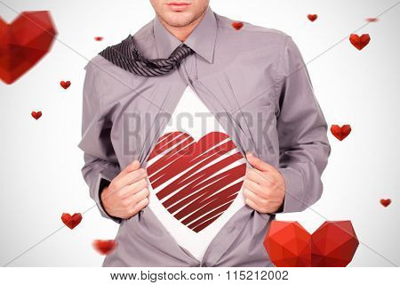 red heart against young attractive man pulling at his tshirt
