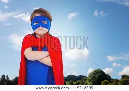 Masked girl pretending to be superhero against park on sunny day