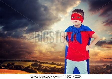 Masked boy pretending to be superhero against country scene