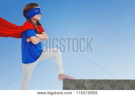 Masked girl pretending to be superhero against blue sky