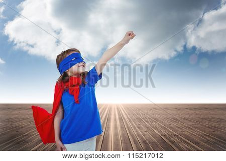 Masked girl pretending to be superhero against cloudy sky background