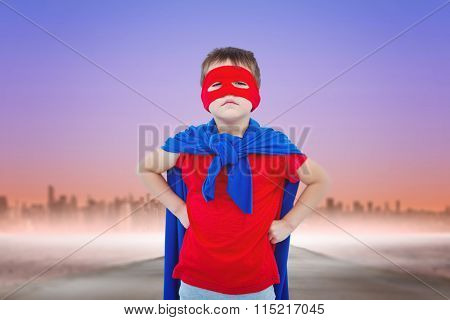 Masked boy pretending to be superhero against fog covered street leading towards skyline