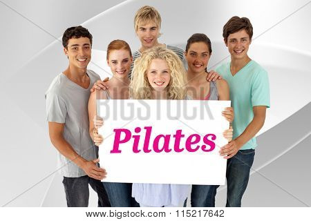 The word pilates and group of teenagers holding a blank card against white angular design