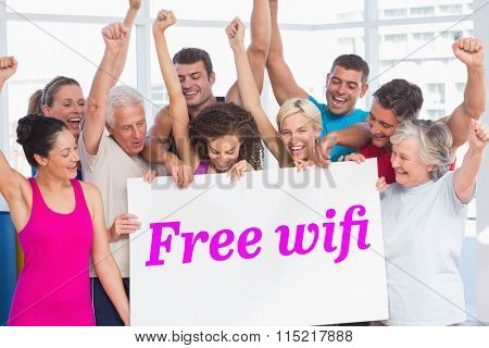 The word free wifi and excited people holding blank billboard at gym against grey wall