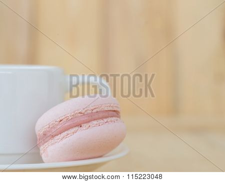 Pink Macaroon With Cup On Wooden Background.