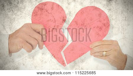Couple holding a broken paper heart against grey background