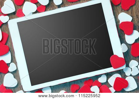 Digital tablet computer with small red hearts