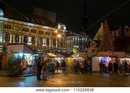 RIGA, LATVIA - DECEMBER 20, 2015: People visit Christmas Fair in old town at evening on December 20, 2015 in Riga, Latvia