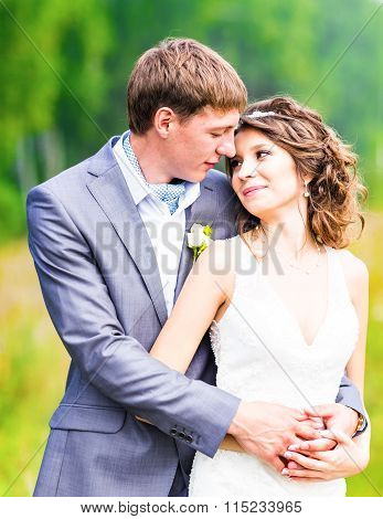 Young wedding couple enjoying romantic moments outside on a summer meadow.
