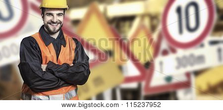 Smiling Worker In Protective Uniform In Front Of Road Signs
