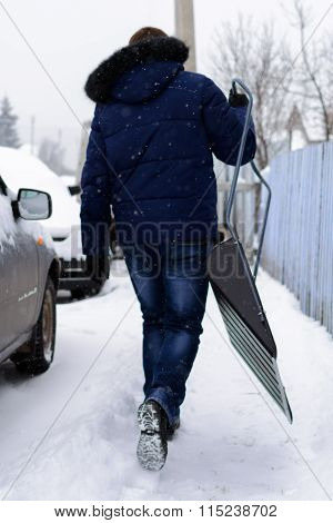 The Young Man Clears Snow In The Yard