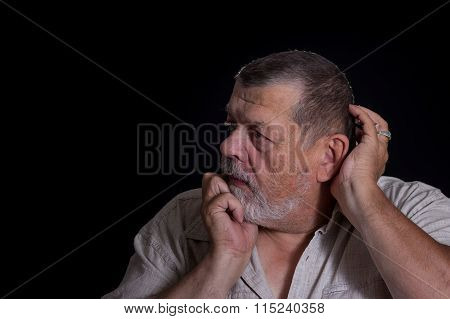Senior man desperately thinking about life problems in the darkness