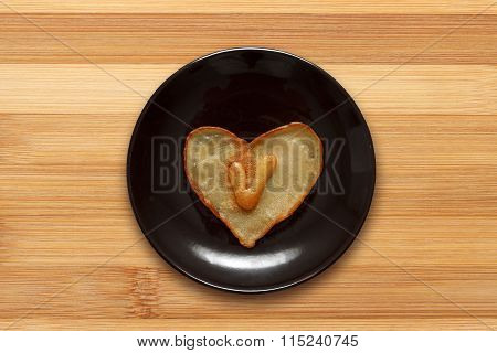 Heart Shaped Pancake With Letter V Inside On Dark Brown Plate On Wooden Background