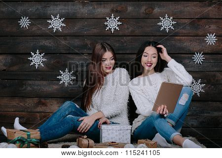 Two beautiful girls with a tablet, between gifts