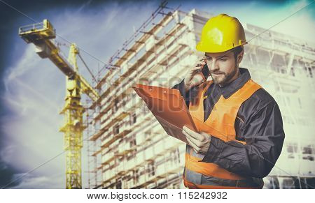 Worker With Protective Uniform In Front Of Construction Scaffolding And Construction Crane