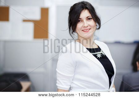 Successful attractive brunette with kind eyes standing in conference room and welcoming smile. Weari
