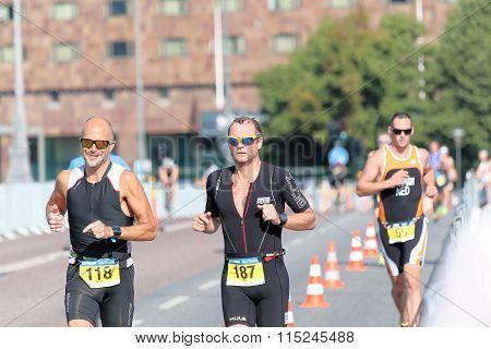 Three Men Running In Bright Wearing Sunglasses, Building Behind