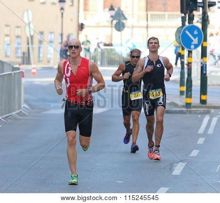 Three Muscular Men Running  On The Street