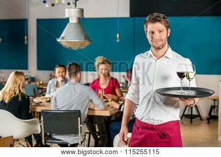 Portrait of confident waiter holding tray at restaurant with customers in background
