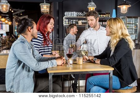 Young waiter serving drinks to customers at table in bar