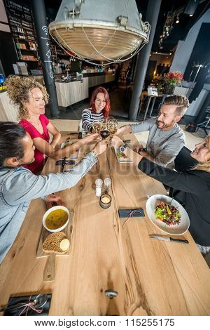 High angle view of friends toasting wineglasses at restaurant table