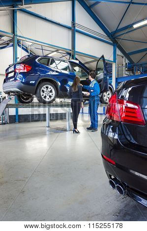 A car is lifted on a bridge in a car garage, the mechanic stands next to it with the owner