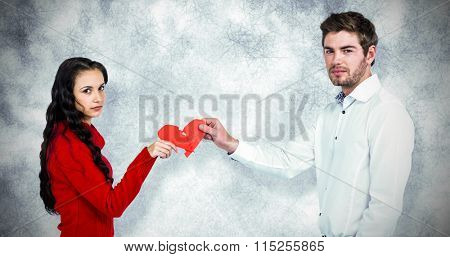 Portrait of couple holding red cracked heart shape against grey background