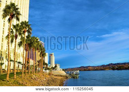 January 16, 2016 in Laughlin, NV:  Pedestrian Riverwalk where tourists can walk to view the majestic river and walk from one casino to another casino which is alongside Hotels, Palm Trees, and the Colorado River taken in Laughlin, NV