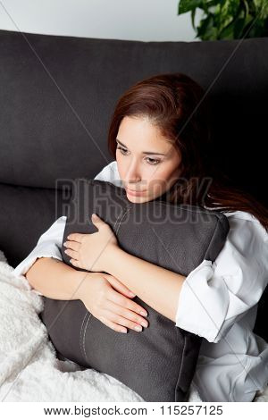 Relaxed young girl hugging a cushion on the sofa at home