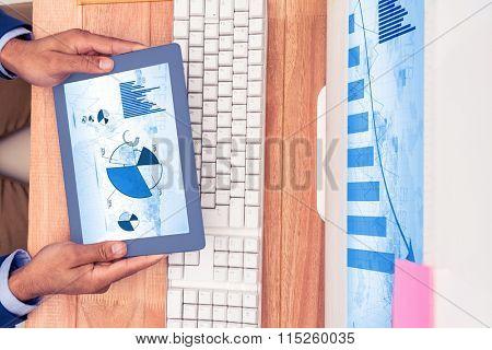 Blue data against businessman holding digital tablet by keyboard at desk