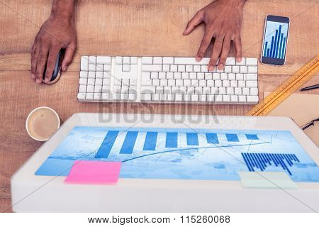 Blue data against businessman using computer while working at desk