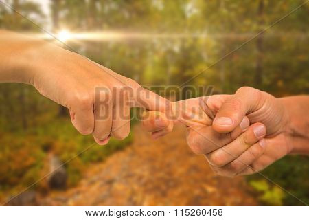 Cropped image of people holding fingers against scenic view of walkway along lush forest