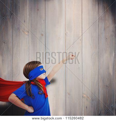 Masked girl pretending to be superhero against wooden planks
